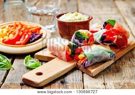 rainbow spring rolls with avocado white bean hummus on a dark wood background