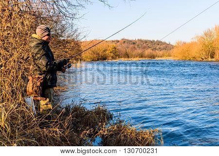 Fisherman on the river bank. Sport fishing, leisure.