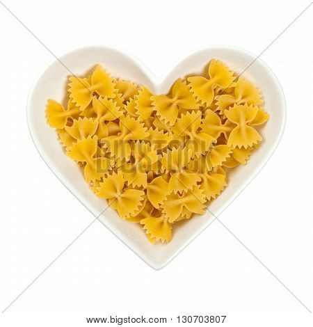 Bow Tie Pasta in Heart Shaped Bowl Isolated on white. Selective focus.