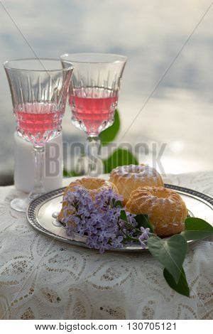 Two glas of pink wine, cakes and lilac on the table outdoors