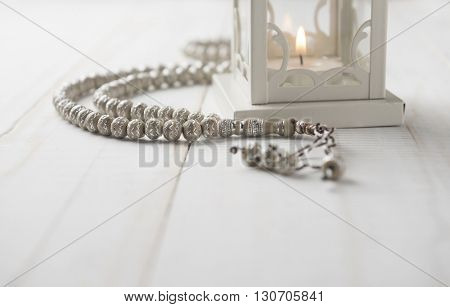 Close up of Islamic prayer beads near candle holder on white background.