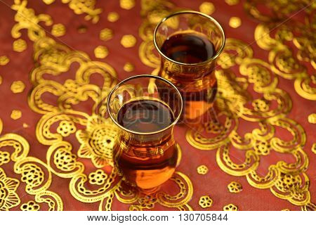 Traditional Arabic tea cups filled with popular black tea on shiny golden background.