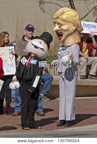 Asheville, North Carolina, USA - February 28, 2016: Parody of Mr. Monopoly holding moneybags cozying up to a happy Hillary Clinton character as Bernie Sanders supporters watch on February 28, 2016 in downtown Asheville, NC