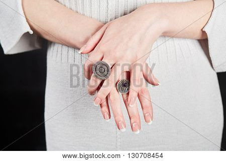 Female hands with signet rings on fingers over white knitted dress.