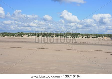 Sandy beach with sand dunes and blue sky in the background