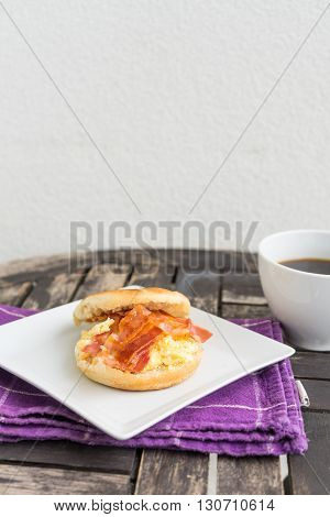 English breakfast. Salt muffin with scrambled eggs bacon and cheese on white plate with dark coffee in white mug lying on wooden background. Unhealthy breakfast with bacon eggs pastry and coffee on purple dishtowel.
