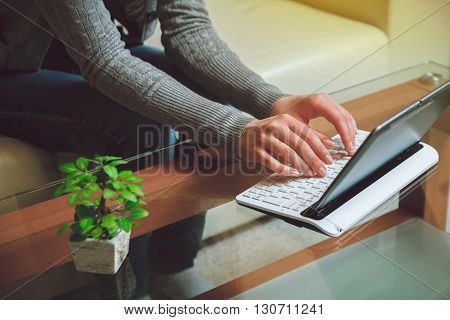Girl sits at a table with a laptop. Telework concept.