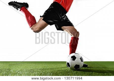 close up legs of football player in red socks and black shoes running and kicking the ball in free kick action playing isolated on white background