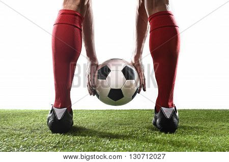 close up legs of football player in red socks and black shoes holding the ball in his hands placing it at the free kick or penalty spot playing on grass pitch isolated on white background poster