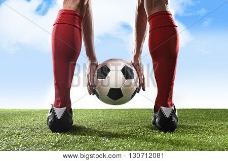 close up legs of football player in red socks and black shoes holding the ball in his hands placing it at the free kick or penalty spot playing outdoors on green grass pitch under a blue sky