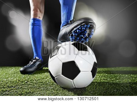 close up legs and feet of football player in blue socks and black shoes playing with the ball standing on green grass pitch isolated on black background with flash lights and lens flare