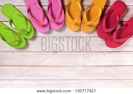Semi circle row of summer flip flops on beach decking background