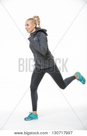 Athletic blonde girl in the sportswear runs on the white background in the studio. She wears cyan-yellow sneakers, black-gray pants and gray hoody. Her left foot is in the air. She looks forward with a smile. She has a plait on her head. Vertical.