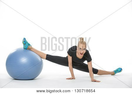 Athletic blonde girl in the sportswear with a blue fitball on the white background in the studio. She wears cyan-yellow sneakers, black pants and black t-shirt. She makes the splits: she leans on her hands while her right leg is on the fitball and left le