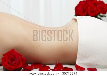 Young woman is about to receive Swedish deep tissue light medium pressure massage. Indoors with red roses.