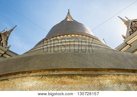 Image of the Golden Stupa of the Temple of Emerald Buddha, known as Wat Phra Keaw on the banks of Chao Phra river in the Grand Palace of Bangkok. The clear, bright sky on the background looks dazzling.