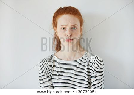 Closeup Portrait Of Grumpy Or Annoyed Young Woman With Red Hair Wearing Striped Top, Looking At The