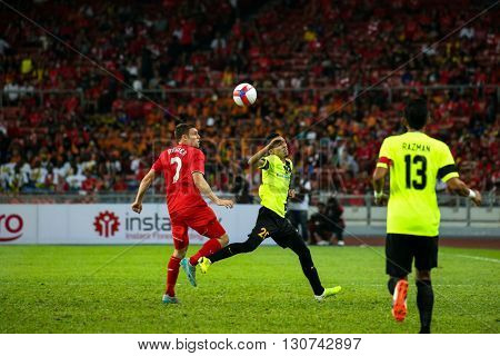 July 24, 2015- Shah Alam, Malaysia: Liverpool's James Milner (red) heads the ball in a friendly match against the Malaysian Team. Liverpool Football Club from England is on an Asia tour.