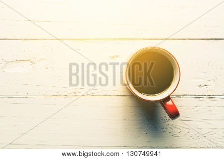 A cup of black coffee on white wood table Overhead view of a cup of black coffee