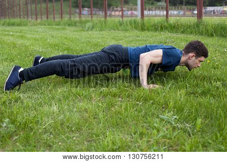 Outdoor fitness workout. Young man doing an exercise in the city park performing push ups on the grass
