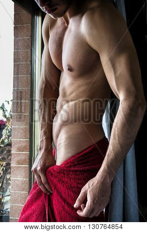 Portrait of sexy shirtless man looking out of window during the day