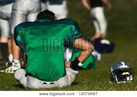 A tired football player is taking rest after the game.