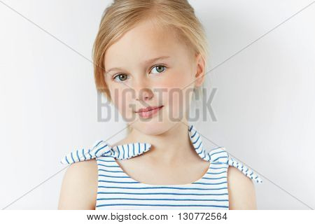 Isolated Headshot Of Adorable Preschool Female Model With Fair Hair Posing In Striped Dress Against