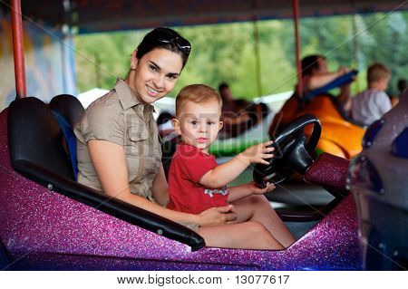 Mother and 2 years old baby pay drive dodgem together in the theme-park.