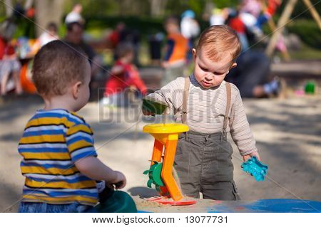 2 years old children are playing together in the sandbox