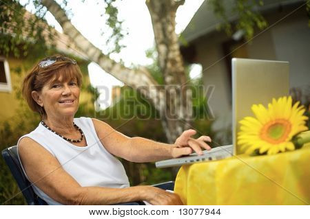 Modern senior woman sitting in the garden at home and using a laptop computer. Summer, outdoor.