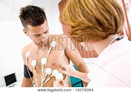 Nurse makes the patient ready for medical EKG test. Real people, real location, not a staged photo with models.
