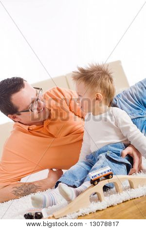 Father and two year old child playing together with wooden toy train. Sitting on floor at home, smiling.