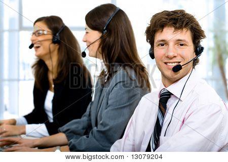 Kundenservice-Team arbeiten in Headsets, lächelnd. Der Mensch im Vordergrund.