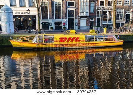 AMSTERDAM NETHERLANDS - 17TH FEBRUARY 2016: A DHL sevice center boat along the Amsterdam Canals during the day.