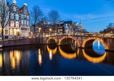 A view of the bridges at the Leidsegracht and Keizersgracht canals intersection in Amsterdam at dusk. Bikes and buildings can be seen.