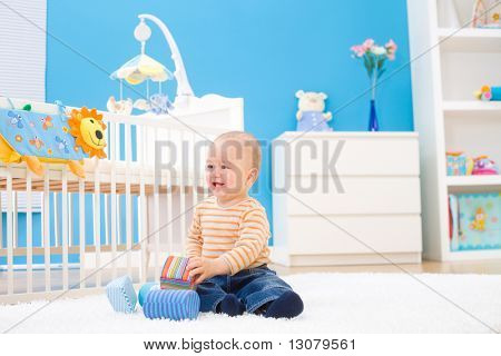 Happy baby boy (1 year old) sitting on floor at children's room and playing with toy blocks. Toys are officially property released.