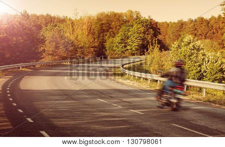 Motobike blurred on asphalt road in beautiful summer evening at countryside