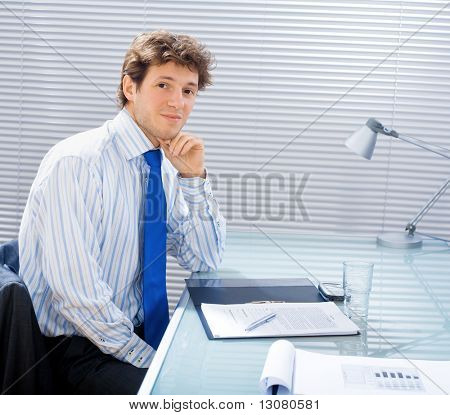 Young handsome businessman sitting by desk at office and working.