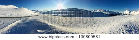 A snowfield is lit by a winter sun low on the horizon.