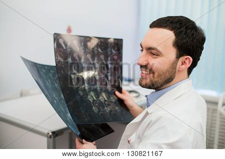 Portrait of a happy caucasian male radiologist holding x-ray while sitting at his office.