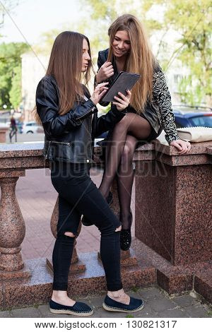 Two young women in the city are looking at the the screen of a tablet and smiling