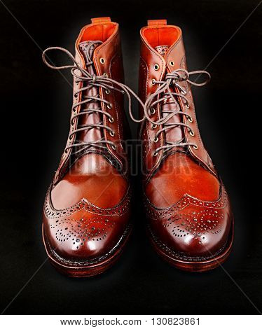 Wingtip dark chili brown dress boots full size isolated on black background