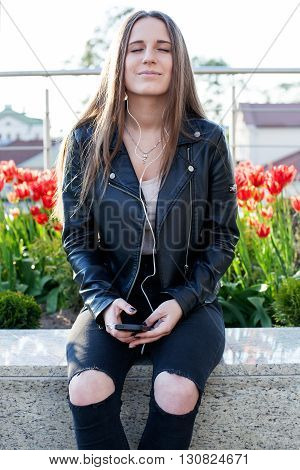 Young beautiful woman is sitting on the stone parapet in the city center and listening to music with closed eyes