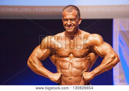 MAASTRICHT THE NETHERLANDS - OCTOBER 25 2015: Male bodybuilder flexes his muscles and shows his best physique in a lats spread pose on stage at the World Grandprix Bodybuilding and Fitness