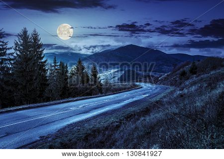 Empty asphalt mountain road with near the coniferous forest with cloudy sky at night in full moon light