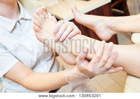 woman under foot massage before pedicure procedure in beauty salon