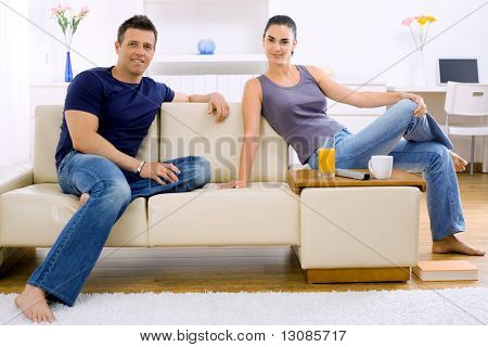 Casual young couple relaxing at home, sitting on a couch.