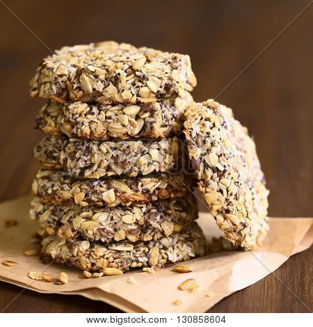 Vegan cookies made of banana oatmeal and roasted oat grains linseed poppy seeds grated coconut chia seeds and cinnamon powder arranged in pile photographed with natural light (Selective Focus Focus on the front of the cookies)