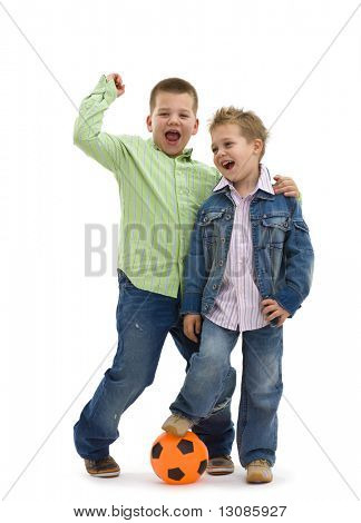 Happy young brothers wearing trendy jeans clothers posing togethers with football, on isolated white background.