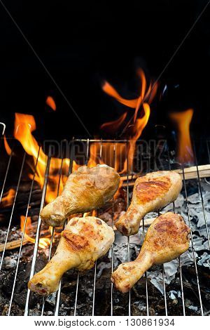 Grill concept.  Marinated Chicken Legs Fried On The Hot BBQ Grill. Charcoal Flames On the Background.